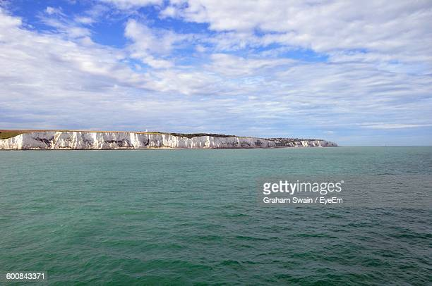 Scenic View Of Sea By White Cliffs Of Dover Against Cloudy Sky