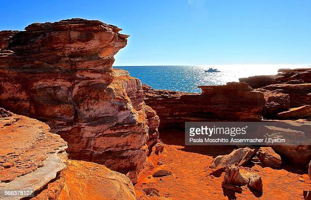 Scenic View Of Sea From Rock Formations In Roebuck Bay Against Clear Blue Sky