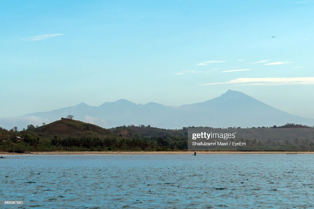 Scenic View Of Sea In Front Of Mountains Against Sky : Stock Photo
