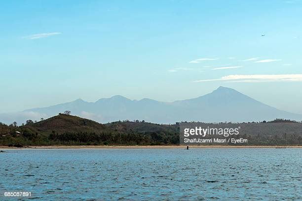 scenic view of sea in front of mountains against sky - shaifulzamri fotografías e imágenes de stock