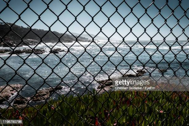 scenic view of sea seen through chainlink fence - christian soldatke stock pictures, royalty-free photos & images