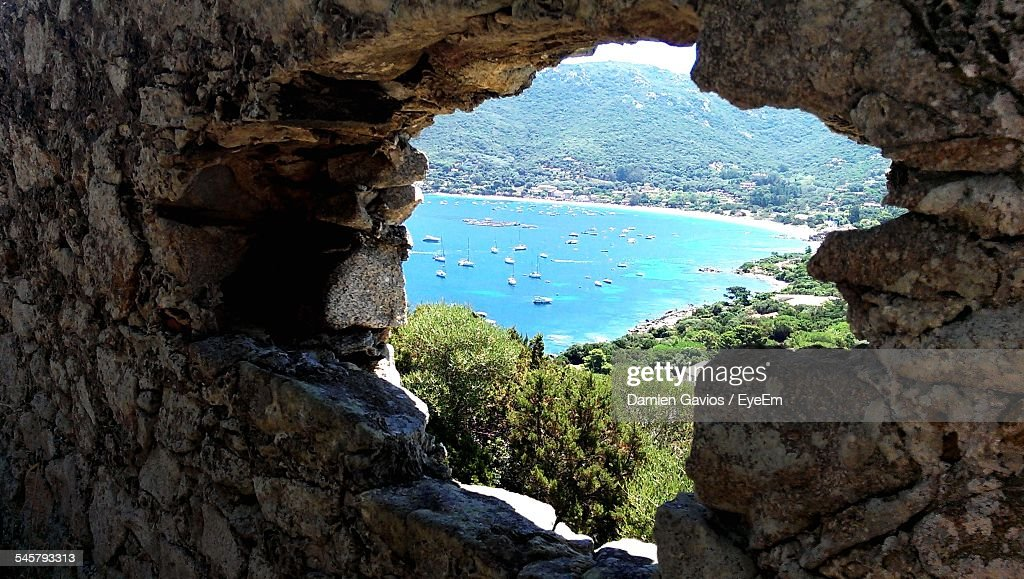 Scenic View Of Sea Seen Through Hole On Stone Wall : Stock Photo