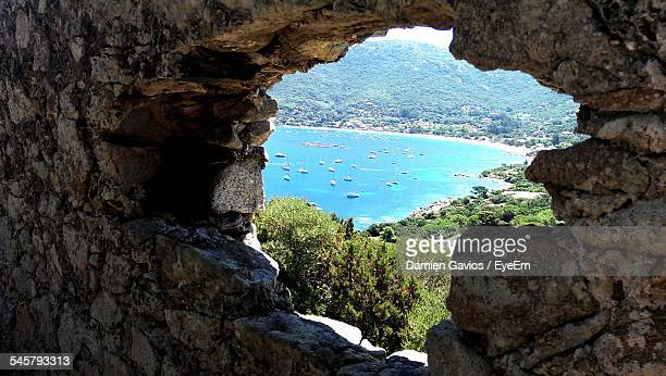scenic view of sea seen through hole on stone wall - corsica stock photos and pictures