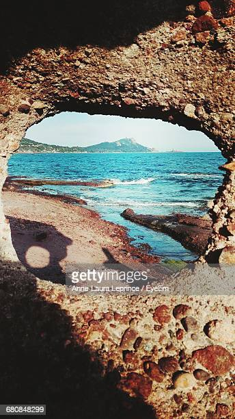 Scenic View Of Sea Seen Through Rock Hole On Sunny Day