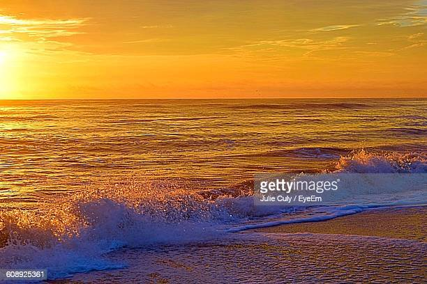scenic view of sea waves rushing towards shore against sky at sunset - julie culy stock pictures, royalty-free photos & images