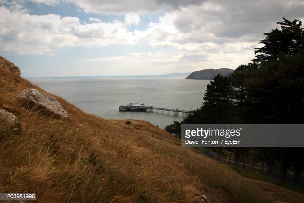 scenic view of sea with pier against sky, llandudno - llandudno wales stock pictures, royalty-free photos & images