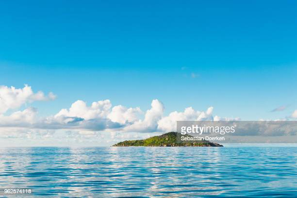 scenic view of seascape against blue sky, island of petite soeur, seychelles - island stock pictures, royalty-free photos & images