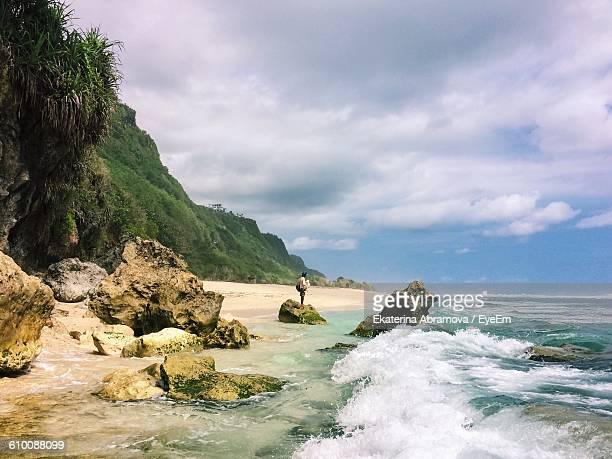 Scenic View Of Shore And Sea Against Cloudy Sky