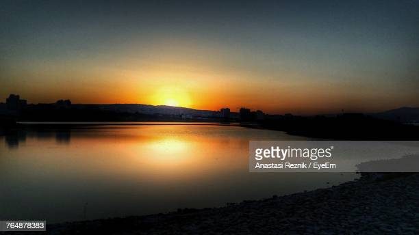 scenic view of silhouette city against sky during sunset - anastasi foto e immagini stock
