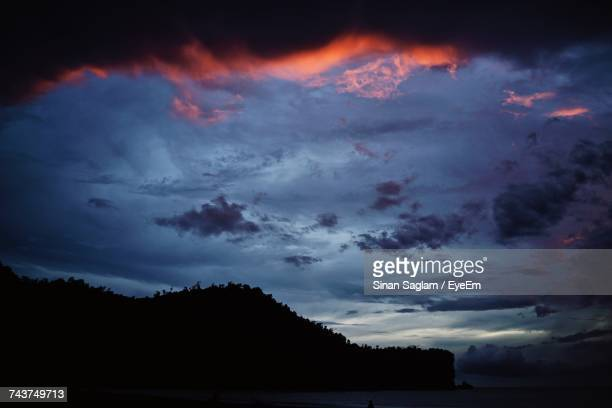 Scenic View Of Silhouette Cliff By Sea Against Cloudy Sky During Sunset