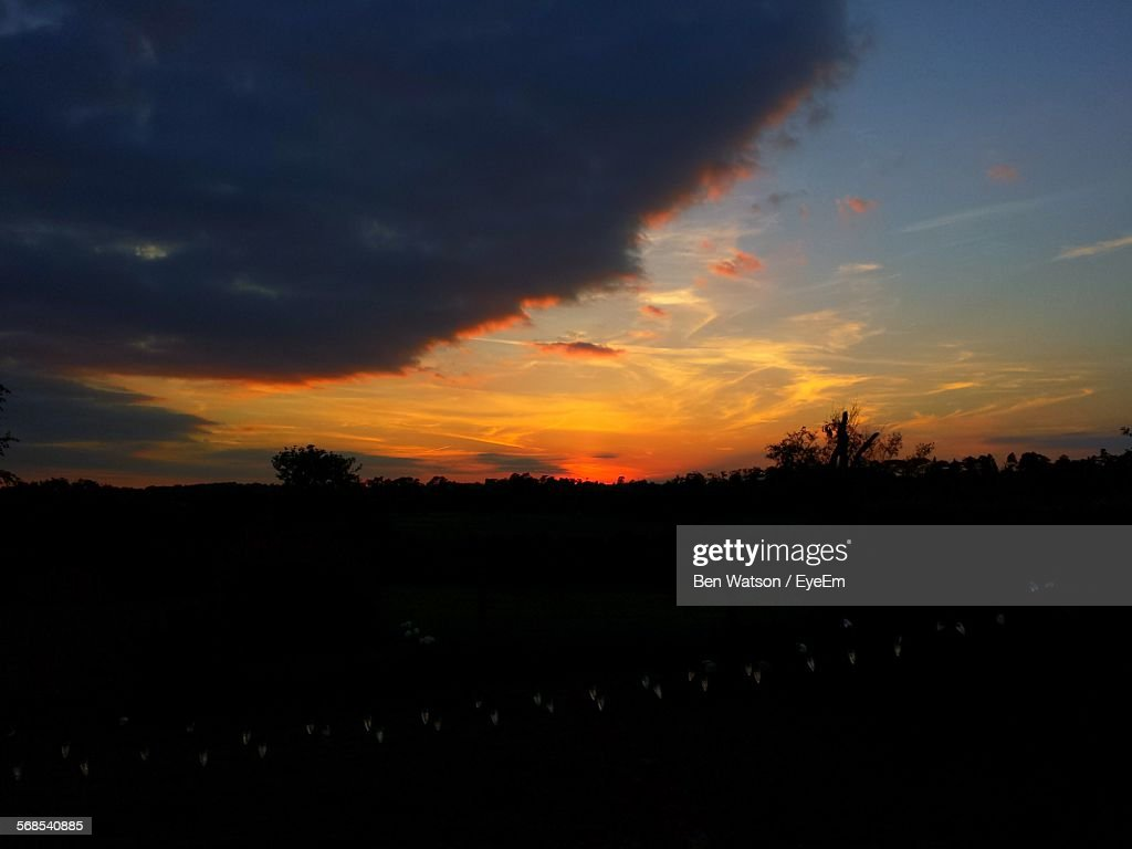 Scenic View Of Silhouette Field Against Cloudy Sky : Stock Photo
