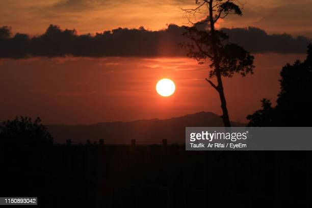 scenic view of silhouette field against orange sky - banda aceh stock pictures, royalty-free photos & images