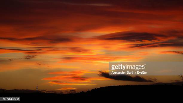 Scenic View Of Silhouette Field Against Orange Sky