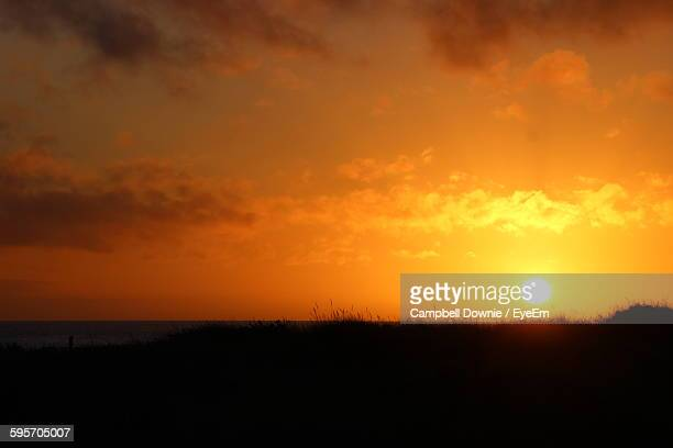 scenic view of silhouette field against sky during sunset - campbell downie stock pictures, royalty-free photos & images