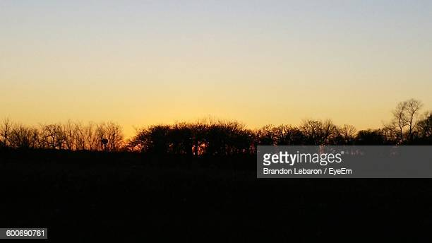 scenic view of silhouette field and trees against sky during sunset - lebaron stock photos and pictures