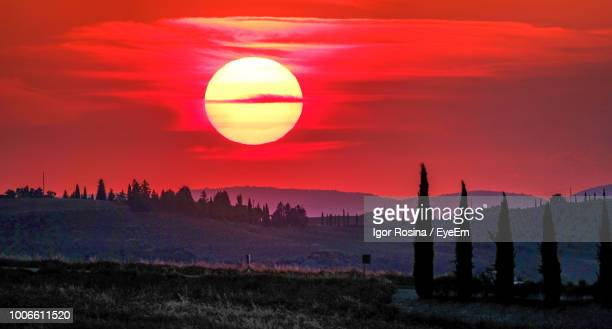 scenic view of silhouette landscape against orange sky - san quirico d'orcia stock pictures, royalty-free photos & images