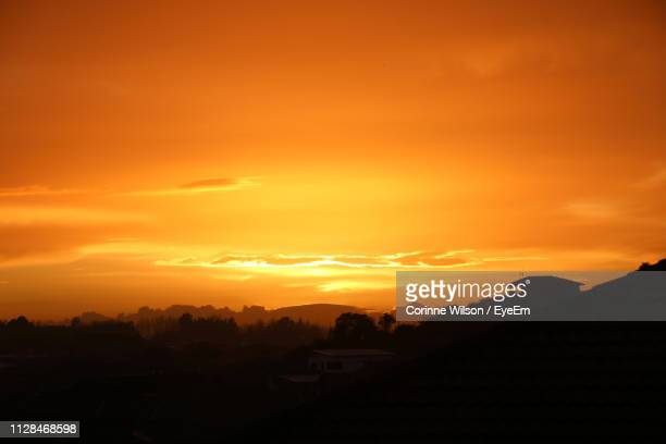 scenic view of silhouette landscape against orange sky - hamilton new zealand stock pictures, royalty-free photos & images