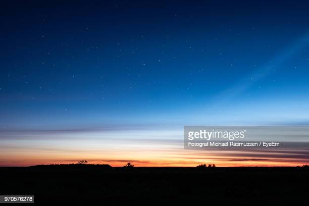 scenic view of silhouette landscape against sky at night - horizon over land stock photos and pictures