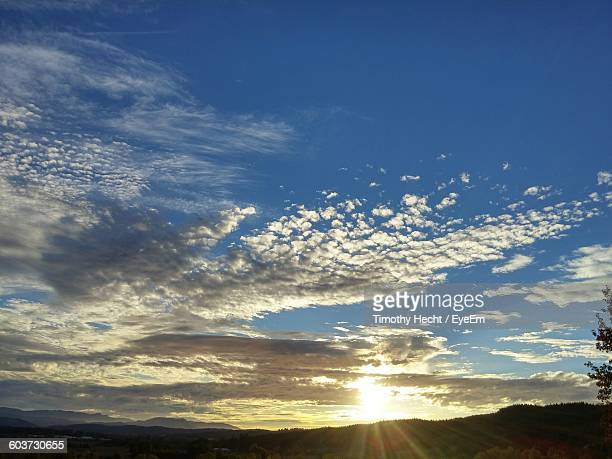 Scenic View Of Silhouette Mountain Against Cloudy Sky During Sunrise