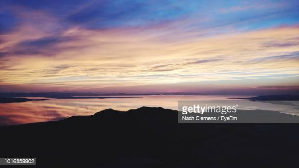 scenic view of silhouette mountain against dramatic sky during sunset - great salt lake stock pictures, royalty-free photos & images