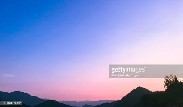 scenic view of silhouette mountains against clear sky at sunset - 夕暮れ ストックフォトと画像