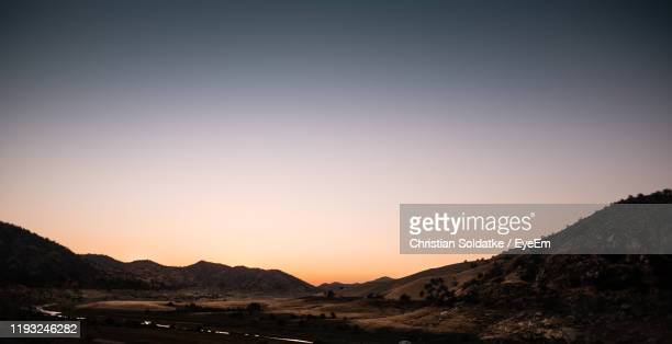 scenic view of silhouette mountains against clear sky during sunset - christian soldatke foto e immagini stock