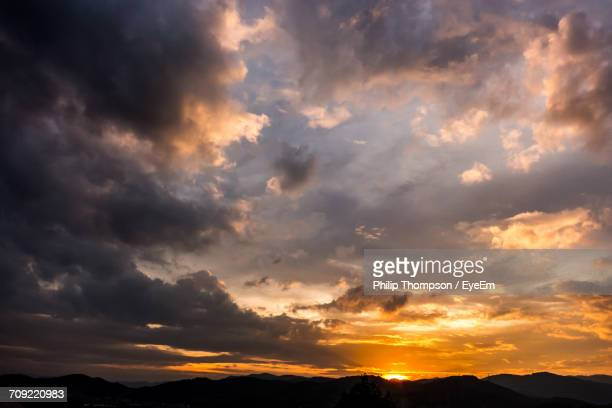 scenic view of silhouette mountains against cloudy sky during sunset - dramatic sky stock pictures, royalty-free photos & images