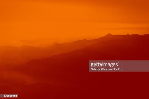 Scenic View Of Silhouette Mountains Against Dramatic Sky During Sunset
