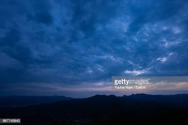 scenic view of silhouette mountains against dramatic sky - avondschemering stockfoto's en -beelden