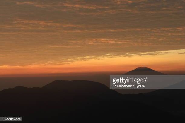 scenic view of silhouette mountains against orange sky - munandar stock pictures, royalty-free photos & images