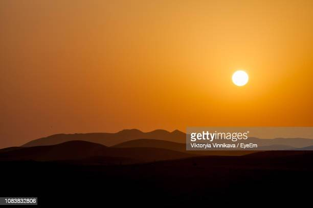 scenic view of silhouette mountains against orange sky - abu dhabi stock pictures, royalty-free photos & images