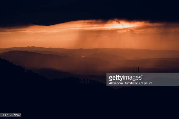 scenic view of silhouette mountains against orange sky - heat haze stock pictures, royalty-free photos & images