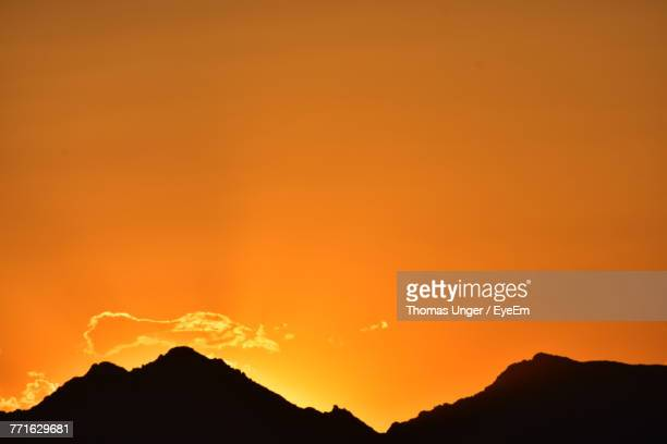 scenic view of silhouette mountains against orange sky - lake havasu stock photos and pictures