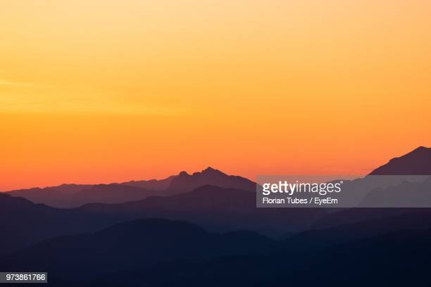 scenic view of silhouette mountains against orange sky - orange sky stock pictures, royalty-free photos & images
