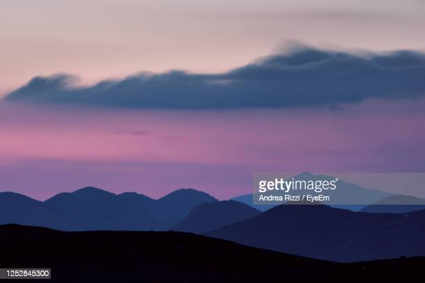 scenic view of silhouette mountains against romantic sky - andrea rizzi fotografías e imágenes de stock