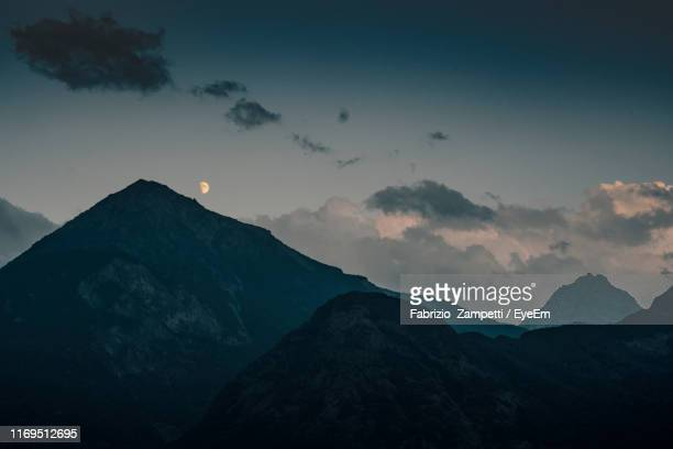 scenic view of silhouette mountains against sky at sunset - fabrizio zampetti foto e immagini stock