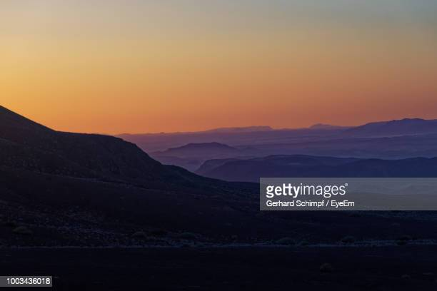 scenic view of silhouette mountains against sky during sunset - gerhard schimpf stock photos and pictures