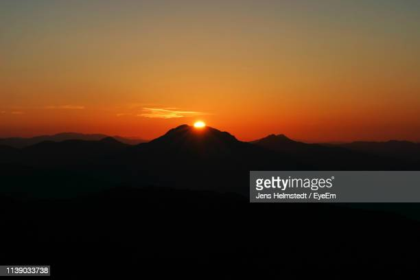 scenic view of silhouette mountains against sky during sunset - jens helmstedt stock-fotos und bilder