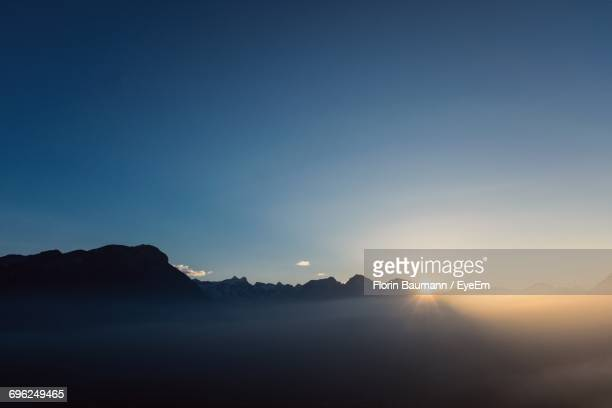 scenic view of silhouette mountains against sky during sunset - schwyz stock pictures, royalty-free photos & images