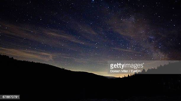 Scenic View Of Silhouette Trees On Hill Against Starry Sky