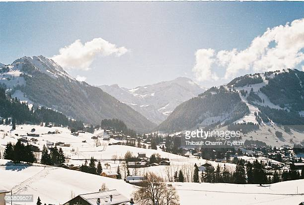 Scenic View Of Ski Town And Snow Covered Mountains Against Sky