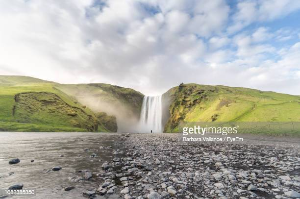 scenic view of skogafoss waterfall on mountain against sky - selfoss stock photos and pictures
