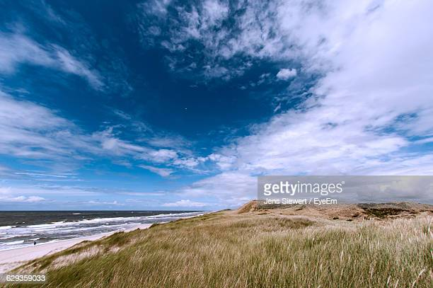 scenic view of sky over sea and field - jens siewert stock-fotos und bilder