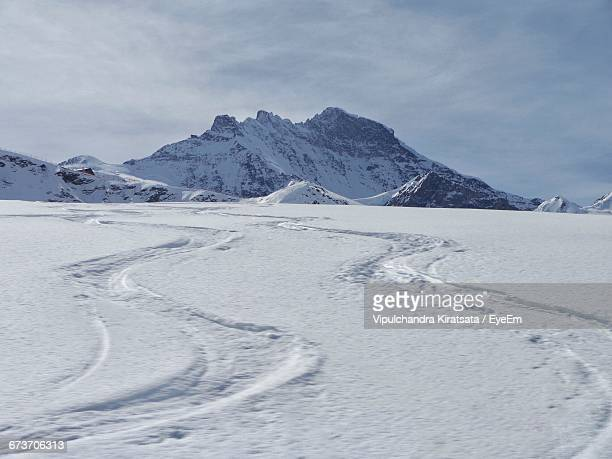 scenic view of snow covered field against mountains - snowfield stock pictures, royalty-free photos & images