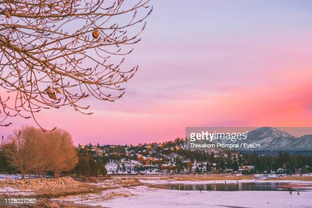 scenic view of snow covered field against sky at sunset - big bear lake stock photos and pictures