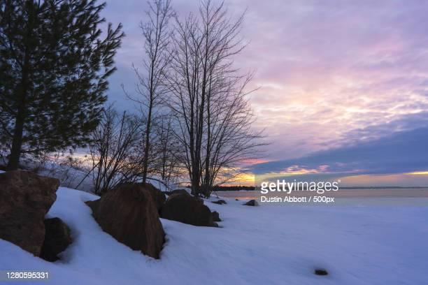 scenic view of snow covered field against sky during sunset, behnke crescent, canada - dustin abbott - fotografias e filmes do acervo