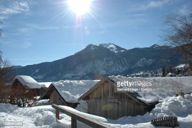 scenic view of snow covered lake, boat houses and mountains against sunny sky - gerhard hagn stock-fotos und bilder