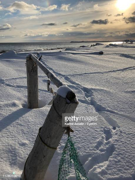 Scenic View Of Snow Covered Land Against Sky During Sunset