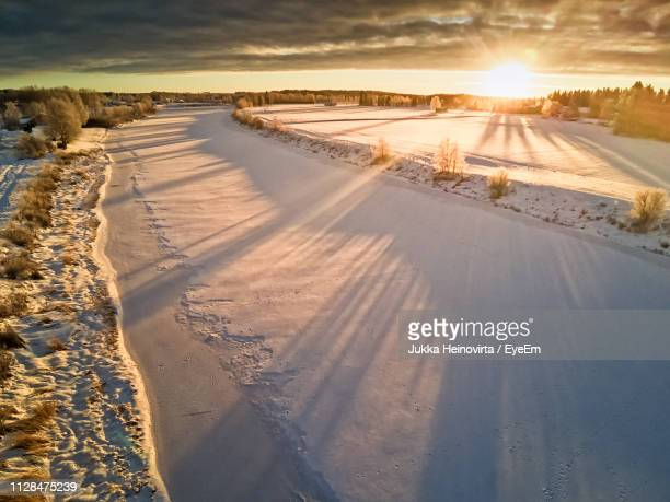 scenic view of snow covered land against sky during sunset - heinovirta stock photos and pictures