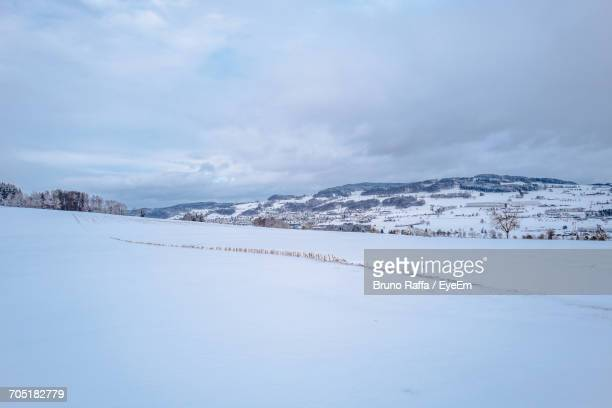 scenic view of snow covered landscape against cloudy sky at knutwil - snowfield stock pictures, royalty-free photos & images